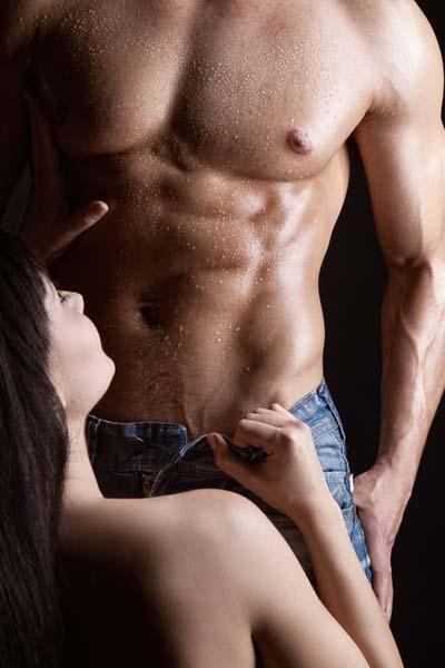 Jeune femme qui déshabille un homme dans le noir